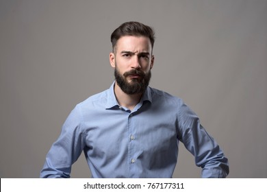 Young serious upset bearded business man with arms on hips and intense look at camera against gray studio background.