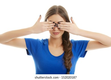 Young serious woman in blue T-shirt covering her eyes with her hands over white background.