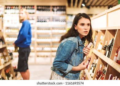 Young serious woman in denim jacket frightenedly looking aside trying steal bottle of wine in modern supermarket