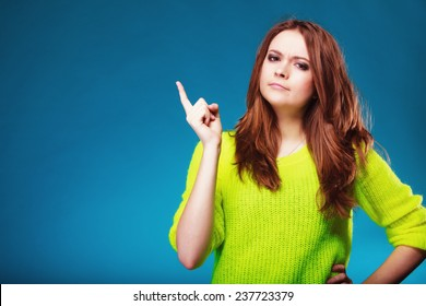 Young serious woman shaking wagging her finger teenage girl scolding on blue