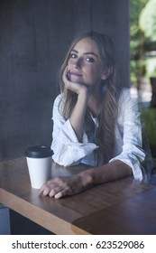 Young serious woman sitting in cafe with coffee photographed through window glass from outside