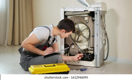 young serviceman checks broken washing machine loader with open back side panel on floor in room closeup