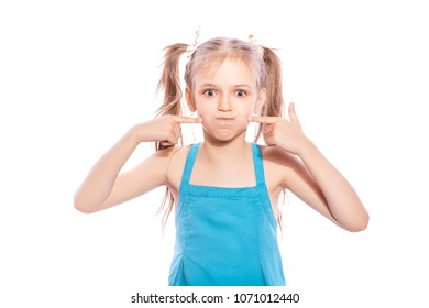 Young seven years old brunette girl in blue dress on a white isolated background. She blows her cheeks, funny emotions on her face