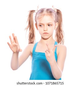 Young seven years old brunette girl in blue dress on a white isolated background. Counting on her fingers, thoughtful emotions on her face