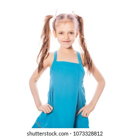 Young seven years old brunette girl in blue dress on a white isolated background. Smile and happiness emotions on her face. Girl miss two front teeth