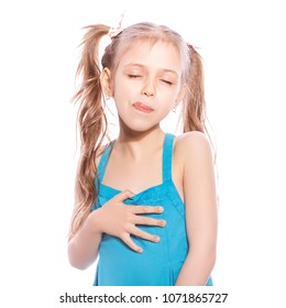 Young seven years old girl in blue dress on a white isolated background. Delightful, joyful emotions on her face, makes yummy, hungry gersture with her hands and face, licking her lips with tongue