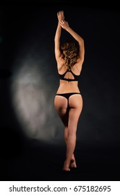 Young sexual woman in black underwear with a slim figure and tanned body is standing on a gray background. Femininity, perfect skin. Unrecognizable, back view. Standing on tiptoe. Pulls hands up.
