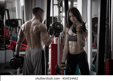 Young sexy athletic man and woman workout with dumbbells in gym. Perfect muscular body