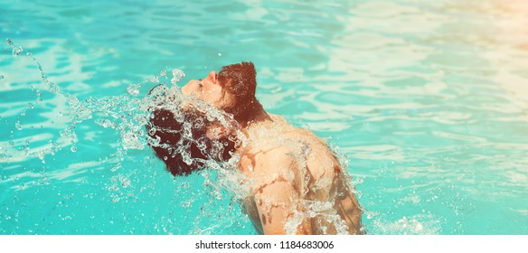 Young sexy bearded man with wet hair and beard swimming in pool with blue water and drops sunny summer day outdoor. Man splashing water by his wet hair and beard on face having fun in swimming pool