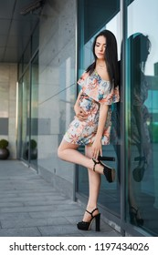 Young sexy beautiful brunette woman with long hair in the street wearing white dress with flower pattern standing near wall with mirrow
