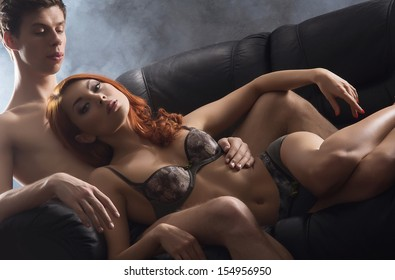 Young, sexy and beautiful couple hugging on the leather sofa at night