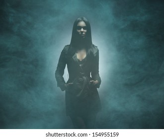 Young, sexy and beautiful woman over smoky background