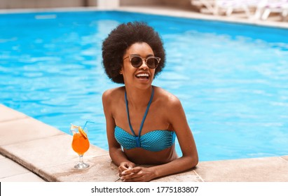 Young sexy black girl with refreshing cocktail having fun and laughing at pool in summer