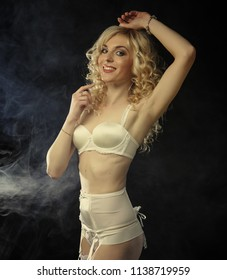 young sexy blond woman in  lingerie over dark background