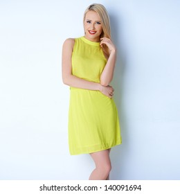 Young and sexy blond woman in yellow dress smiling while isolated on white