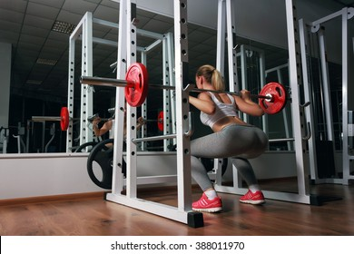 Young sexy blonde european girl in the gym doing squat with barbell in front of the mirror. She is dressed in sports clothes (white top, gray leggings, orange sneakers)