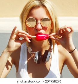 Young sexy blonde girl eating red ice cream in summer hot weather in round sunglasses and white earphones have fun and good mood looking in camera and smiling