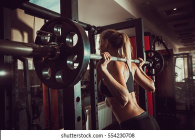 Young sexy blonde girl in the gym preparing to do squat.