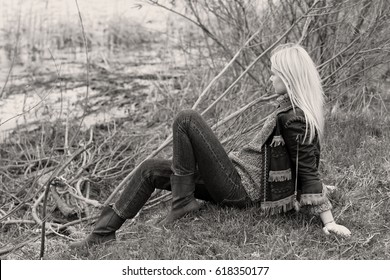 Young sexy blonde girl in nature and reeds near a river and trees in American country style in a leather jacket, sweater blue jeans and brown boots with a beautiful face and pretty eyes