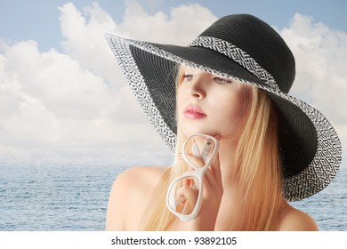 Young sexy blonde girl in sun-hat at sea beach looking sidewards