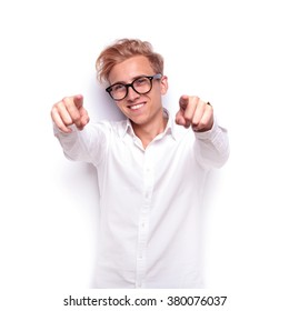 young sexy blonde man pointing both fingers at the camera while looking away wearing glasses in white isolated studio background