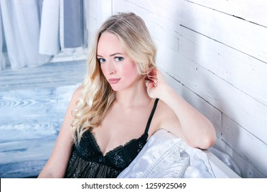 Young sexy blonde woman in a black peignoir with glitter is sitting on a white bed in the photostudio