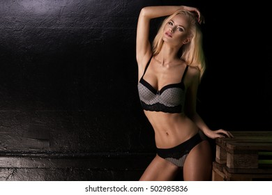 Young sexy blonde woman in dark lingerie