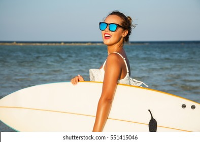 Young sexy blonde woman with long curly hairs and sportive tanned body. Smiling and  posing with surf board near blue ocean in sunny summer day. Wearing stylish mirrored sunglasses. Ready for surfing