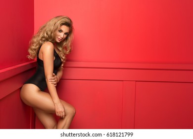 Young sexy blonde woman in red room