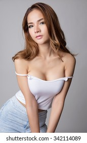 Young sexy brunette asian woman in white tank top and light blue jeans