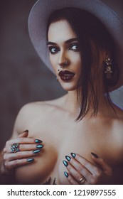 Young sexy brunette naked woman in hat portrait. With tattoo on body and piercings on face.