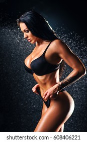 Young sexy brunette wet woman fashion portrait. Rain effect. Tattoo on body.