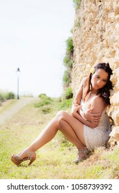 Young sexy brunette woman crouching on the ground against the wall with one leg extended. Dress with miniskirt outdoors.