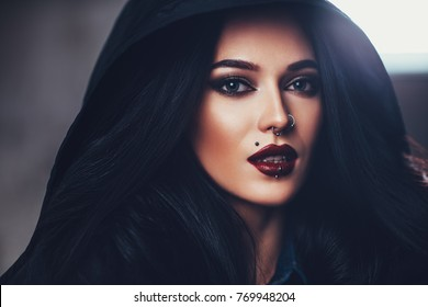 Young sexy brunette woman with piercings portrait in hood