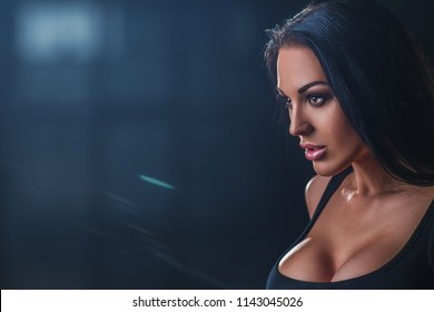 Young sexy brunette woman portrait on dark background with light rays effect