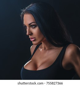 Young sexy brunette woman portrait on dark background