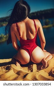 Young sexy brunette woman in red lingerie sitting on beach back view