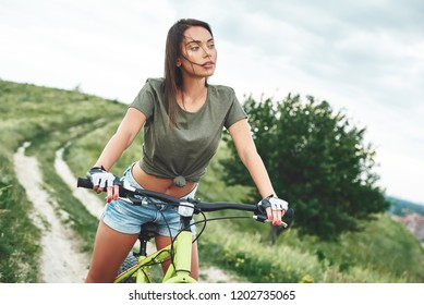 Young sexy brunette woman is riding a bike. She looks at the lovely cloudy sky