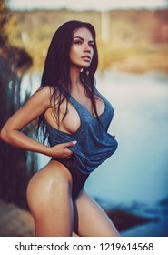 Young sexy brunette woman standing on river beach summer portrait