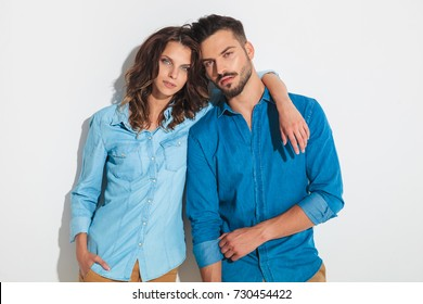young sexy casual couple posing embraced against studio wall