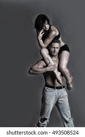 young sexy couple of handsome muscular man in jeans with bare torso holds pretty flexible woman or girl dancing contemporary or modern gymnastic dance in studio on grey background, copy space