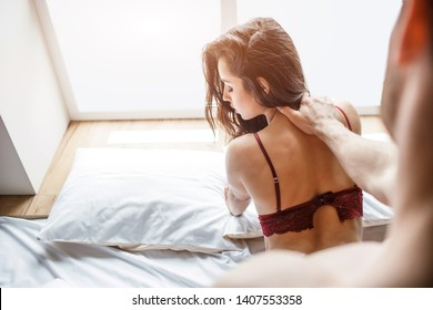 Young sexy couple have intimacy on bed. Guy stand and hold woman in lingerie on neck. Passionate brunette lookback. Hair on face. Love and lust. Intimacy process. Bra semi-opened.