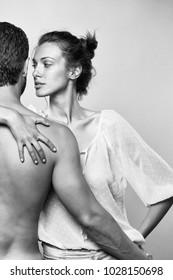 young sexy couple of muscular man embracing with back and pretty woman or girl with brunette hair in white blouse in studio on grey background