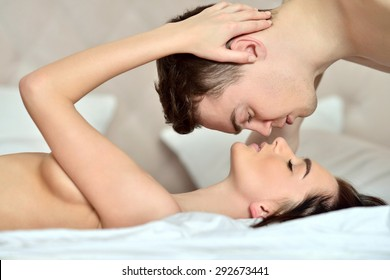 Young sexy couple on the bed. Beautiful lady and guy in erotic pose. Portrait of girl and boy indoors. Cute woman and handsome man are hugging each other. Beauty naked models