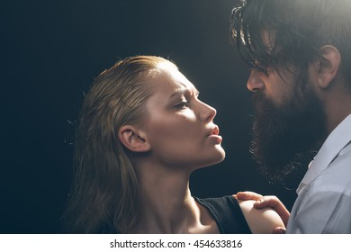 young sexy couple of pretty woman with blonde wet hair and handsome bearded man with long beard embracing on dark studio background