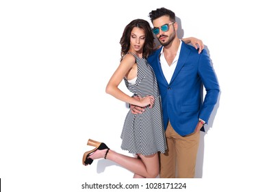 young sexy couple standing together, woman with leg up on white wall
