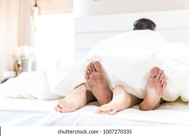 young sexy couples in love lying in bed in hotel, embracing on white sheets, close up legs, romantic mood