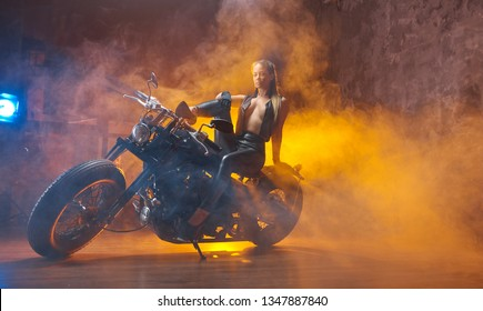 Young sexy curly woman brunette sitting on motorcycle studio installation