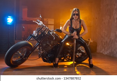 Young sexy curly woman brunette sitting on motorcyclewith sword in hand, studio installation