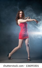 Young sexy dancing woman in red dress with flashes on background with smoke
